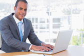 Cheerful businessman working on his laptop — Stock Photo