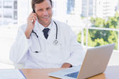 Happy doctor phoning in his office — Stock Photo