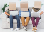 Designers working on laptops with boxes over their head — Stock Photo