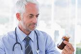Doctor looking at medicine jar — Stock Photo