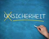 Hand crossing out german word unsicherheit — Stock Photo