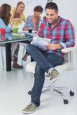 Улыбаясь, дизайнер работает в своем кабинете — Стоковое фото