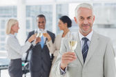 Businessman smiling at camera holding champagne — Stock Photo