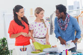 Three fashion designers looking at sketchpad — Stock Photo