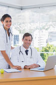 Cheerful doctors posing together in their office — Stock Photo