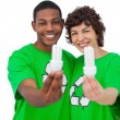 Two environmental activists holding energy saving light bulbs — Stock Photo #26980307