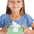 Cheerful little girl holding a wrapped gift — Stock Photo