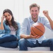 Woman annoyed by her partner watching basketball game — Stock fotografie