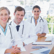 Cheerful doctors posing at their desk — Stock Photo #26980595