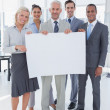 Happy business team holding large blank poster — Stock Photo