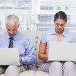 Business sitting on sofa using their laptops — Stock Photo #26980923
