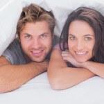 Cheerful couple under the duvet — Stock Photo