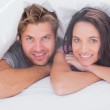 Cheerful couple under the duvet — Stock Photo