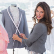 Stock Photo: Attractive fashion designer measuring blazer