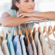 Fashion designer leaning on clothes rail — Stock Photo