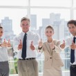 Smiling team of business giving thumbs up — Stock Photo #26981127
