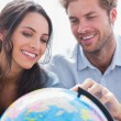 Happy couple looking at a globe — Stock Photo #26981157
