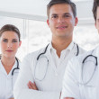 Three smiling doctors with lab coats — Stock Photo #26981337