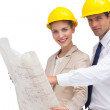 Architects with construction plan and yellow helmets — Stock Photo #26981339