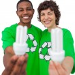 Activists holding energy saving light bulbs — Stok fotoğraf