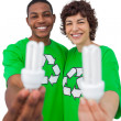 Activists holding energy saving light bulbs — Stock Photo