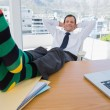 Smiling businessman having a nap with feet on the desk — Stock Photo