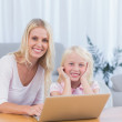 Smiling mother using laptop with her daughter — Stock Photo #26981913