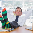 Cheerful businessman relaxing with feet on his desk — Stock Photo
