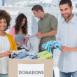 Team of volunteers taking out clothes from a donation box — Stock Photo