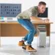 Handsome employee skating through the office — Stock Photo