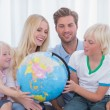 Family looking at globe together — Stock Photo #26982683