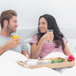 Beautiful couple having breakfast in bed — Stock Photo