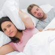 Woman covering ears with pillow while her husband is snoring — Stock Photo #26983017