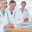 Happy doctors posing at their desk — Stock Photo