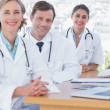 Stock Photo: Happy doctors posing at their desk