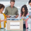 Happy team of volunteers taking out clothes from a donation box — Stock Photo #26983361