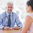 Attractive doctor sitting in front of patient — Stock Photo #26983385