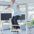 Stock Photo: Creative designer surfing his swivel chair