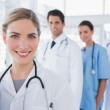 Woman doctor in front of her colleagues — Stock Photo