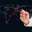 Businessman drawing world map with arrows — Stock Photo #26984477