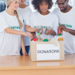 Volunteers putting food in donation box — Stok fotoğraf