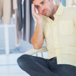 Bored man sitting in a clothing store — Stockfoto