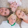 Stock Photo: Overhead of family lying on the carpet