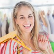 Stock Photo: Cheerful womstanding in clothing store