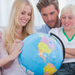 Smiling family with globe — Stock Photo #26985961