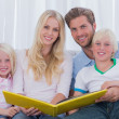 Portrait of a family holding a story book — Stock Photo