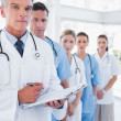 Serious doctor holding clipboard and standing in front of his medical team — Stock Photo #26986707