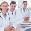Cheerful doctors posing at their desk — Stock Photo