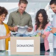 Young team of volunteers taking out clothes from a donation box — Stock Photo #26988339