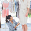 Stock Photo: Fashion designer adjusting dress